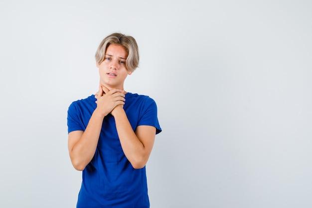 Przystojny nastoletni chłopak cierpiący na ból gardła w niebieskiej koszulce i wyglądający na zaniepokojonego. przedni widok.