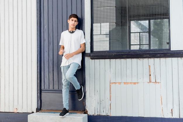 Przystojny nastoletni chłopak opiera na falistej żelaznej bocznicy patrzeje kamerę