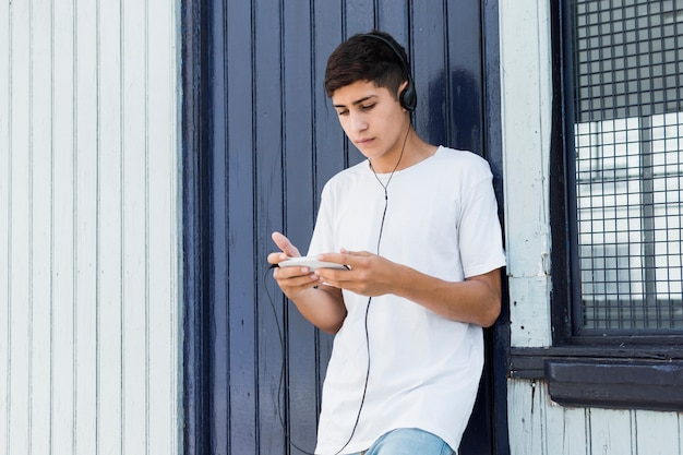 Przystojny nastoletni chłopak opiera na metal ścianie używać smartphone i słuchającą muzykę
