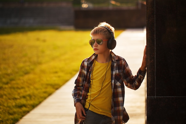 Przystojny nastoletni chłopak słucha muzyka i używa telefon na zmierzchu