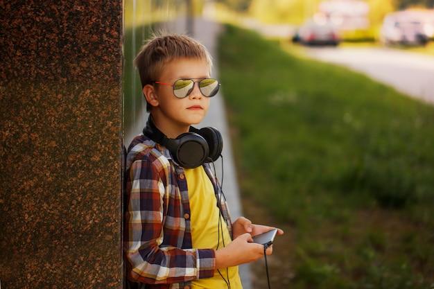 Przystojny nastoletni chłopak słucha muzyka i używa telefon