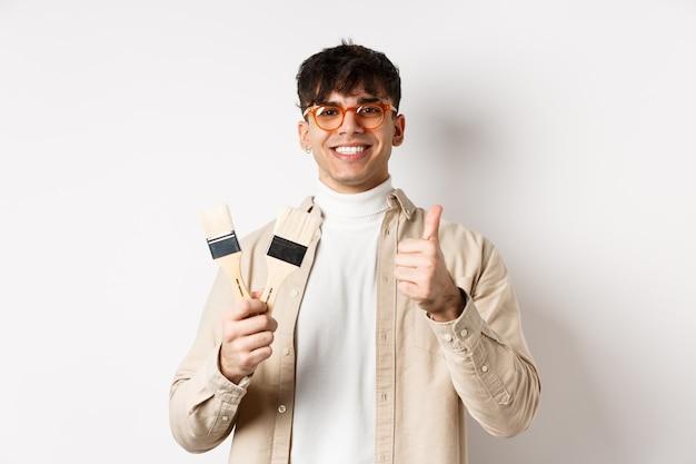 Przystojny, naturalny facet w okularach polecający sklep, pokazujący pędzle do renowacji i wystroju, z aprobatą robi kciuki do góry, stojąc na białej ścianie.