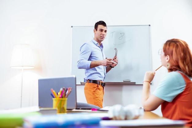 Przystojny nauczyciel. miły młody człowiek zdejmując okulary stojąc przy tablicy