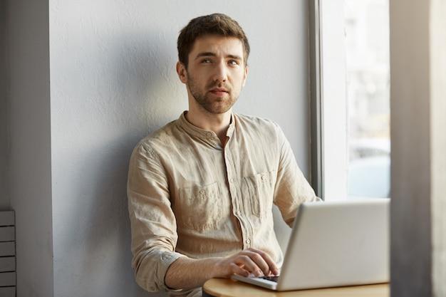 Przystojny, nieogolony facet o ciemnych włosach, pracujący w biurze coworkingowym przy oknie, wyglądający na bok z zamyślonym wyrazem twarzy, próbujący sobie przypomnieć rzeczy, które powinien zrobić.