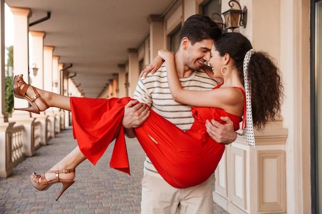 Przystojny nieogolony mężczyzna niosący szczęśliwą kobietę w rękach i uśmiechający się podczas spaceru w pobliżu pięknego budynku