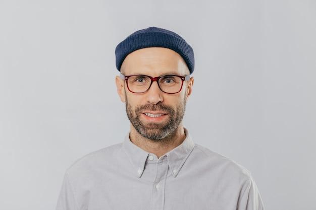 Przystojny, nieogolony mężczyzna nosi przezroczyste okulary, formalną koszulę