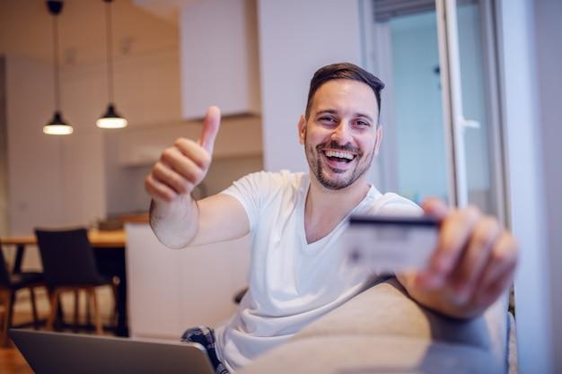 Przystojny nieogolony uśmiechnięty caucasian mężczyzna siedzi na kanapie w żywej pokoju trzyma kredytową kartę w piżamie podczas gdy dawać aprobatom