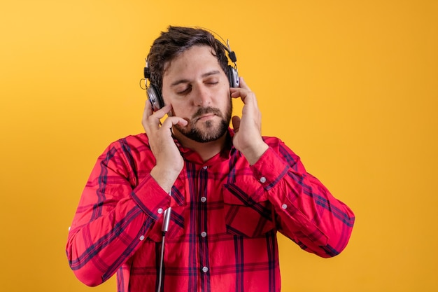Przystojny nowoczesny mężczyzna słuchanie muzyki w słuchawkach na żółto