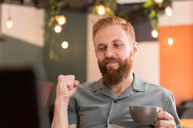 Przystojny nowoczesny mężczyzna trzyma filiżankę kawy