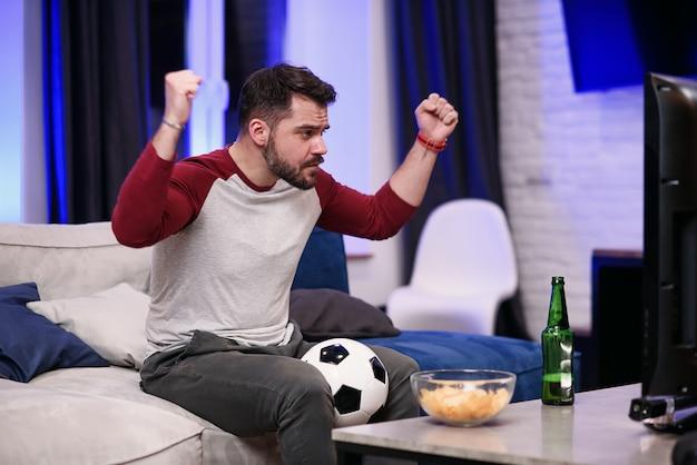 Przystojny, nowoczesny pozytywny 30-letni facet z zadbaną brodą delektuje się chipsami podczas emocjonalnego przeglądu gry ulubionej drużyny futbolowej w telewizji w domu