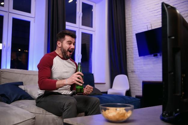 Przystojny, nowoczesny pozytywny facet z zadbaną brodą delektuje się chipami podczas emocjonalnego przeglądu gry ulubionej drużyny futbolowej w telewizji w domu