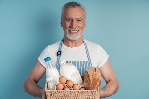 Przystojny, od lat starszy mężczyzna trzymający kosz z jedzeniem chleb, mleko, jajka