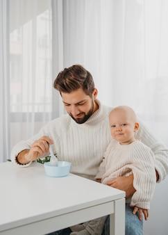 Przystojny ojciec karmi swoje dziecko