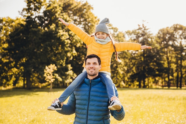 Przystojny ojciec nosi anorack daje piggyback do swojej małej zabawnej dziewczyny