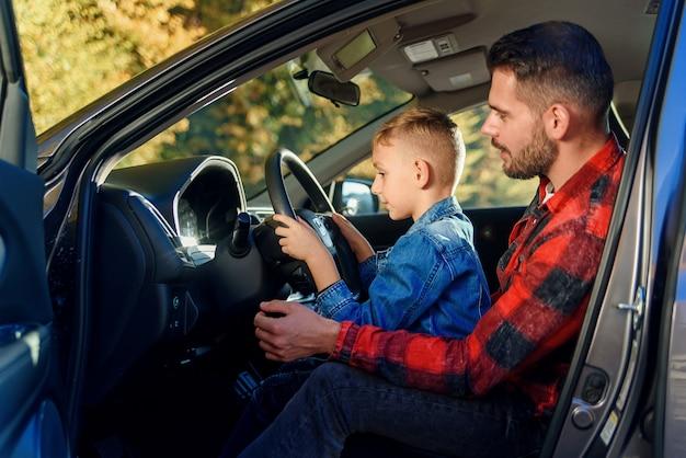 Przystojny ojciec wskazuje na coś podczas gdy uczący nastoletniego syna jeżdżenia samochód