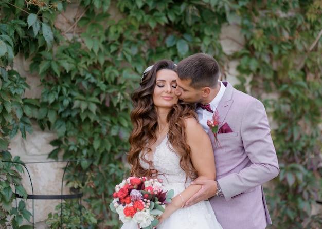 Przystojny pan młody całuje piękną pannę młodą na zewnątrz ubraną w modne stroje ślubne