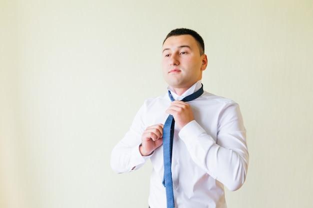 Przystojny pan młody w białej koszuli stawia krawat. pan młody