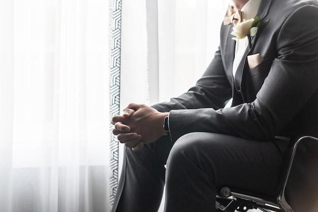Przystojny pan młody w czarnym garniturze modli się przed ceremonią ślubną