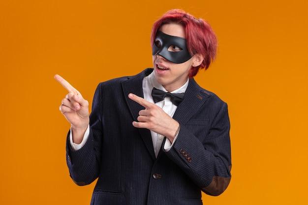 Przystojny pan młody w garniturze, ubrany w muszkę i maskę maskującą, patrzący na bok, uśmiechający się radośnie wskazujący palcami wskazującymi na bok, stojący nad pomarańczową ścianą