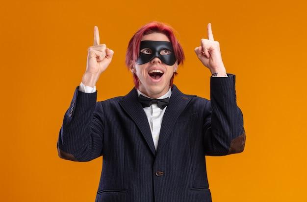 Przystojny pan młody w garniturze, ubrany w muszkę i maskę maskującą, patrzący w górę szczęśliwy i wesoły, wskazujący palcami wskazującymi w górę