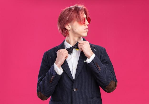 Przystojny pan młody w garniturze w muszce i okularach, patrzący na bok z pewnym siebie wyrazem, który mocuje muszkę stojącą nad różową ścianą