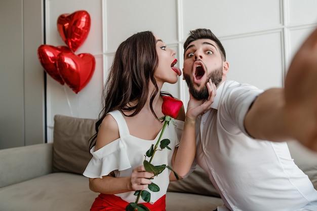 Przystojny para mężczyzna i kobieta co selfie z czerwoną różą i balony w kształcie serca w domu na kanapie