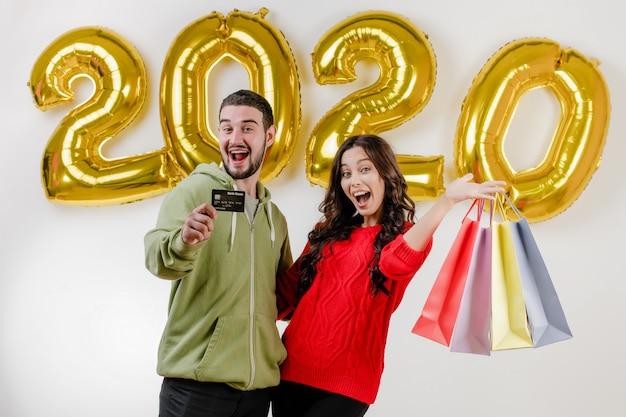 Przystojny para mężczyzna i kobieta trzyma karty kredytowej i kolorowe torby na zakupy przed 2020 balonów