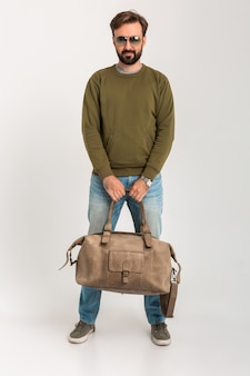 Przystojny, pewnie brodaty stylowy mężczyzna w bluzie z torbą podróżną, na sobie dżinsy i okulary przeciwsłoneczne na białym tle