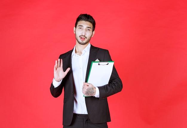 Przystojny pewny siebie biznesmen ubrany w garnitur i trzymający notatnik