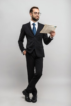 Przystojny, pewny siebie biznesmen w garniturze stojący na białym tle nad szarą ścianą, czytający gazetę, noszący okulary