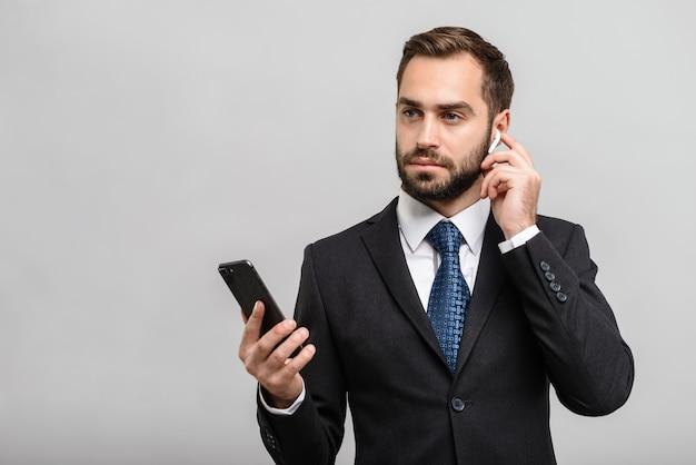 Przystojny, pewny siebie biznesmen w garniturze stojący na białym tle nad szarą ścianą, słuchający muzyki przez słuchawki i telefon komórkowy