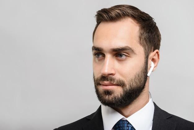 Przystojny, pewny siebie biznesmen w garniturze stojący na białym tle nad szarą ścianą, słuchający muzyki przez słuchawki