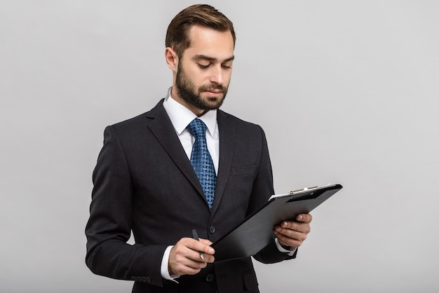 Przystojny, pewny siebie biznesmen w garniturze stojący na białym tle nad szarą ścianą, trzymający notatnik