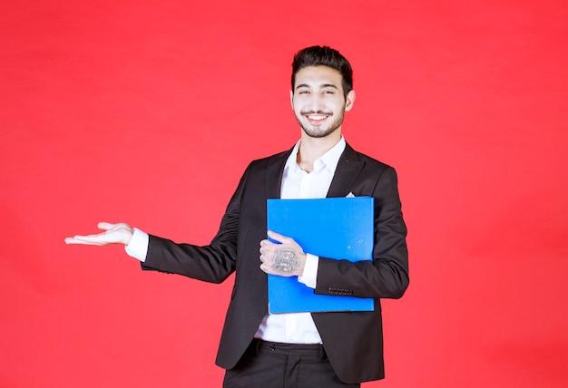 Przystojny pewny siebie biznesmen w garniturze z notatnikiem pokazującym otwartą dłoń