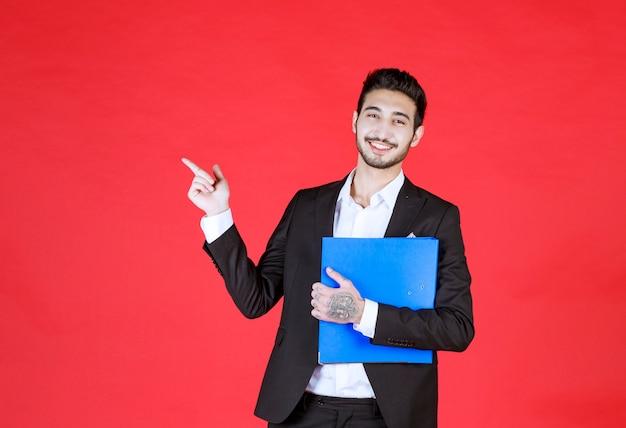 Przystojny pewny siebie biznesmen w garniturze z notatnikiem wskazującym na bok