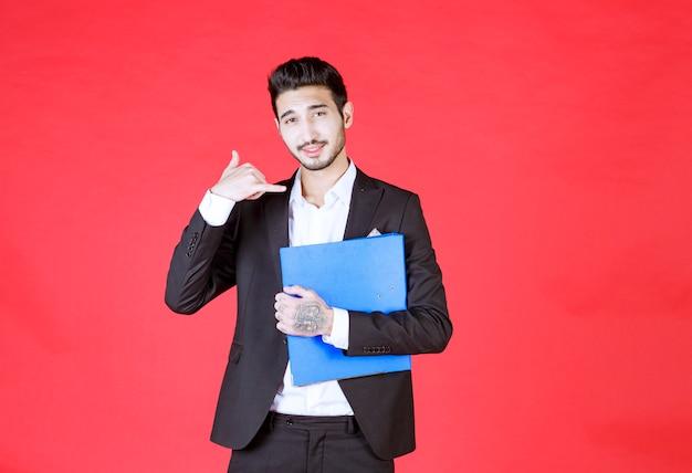 Przystojny pewny siebie biznesmen w garniturze z notatnikiem wykonującym gest połączenia telefonicznego