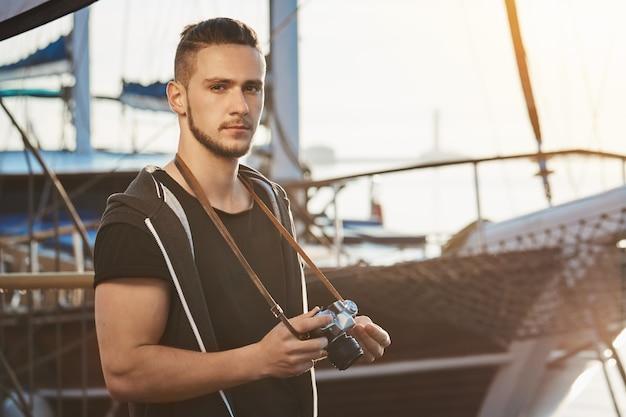 Przystojny, pewny siebie facet ze stylową fryzurą stojący w pobliżu wspaniałego jachtu, trzymający aparat, wpatrujący się poważnie i skupiony podczas sesji zdjęciowej w porcie, robiąc zdjęcia scenerii