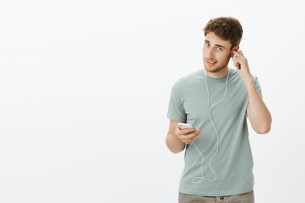 Przystojny, pewny siebie kaukaski mężczyzna z włosiem, zakłada słuchawki i trzyma smartfon, wybiera piosenkę i przygotowuje się do spaceru z muzyką w uszach
