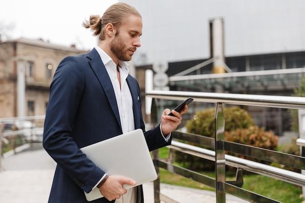 Przystojny, pewny siebie młody brodaty biznesmen stojący na zewnątrz na ulicy, używający telefonu komórkowego podczas noszenia laptopa