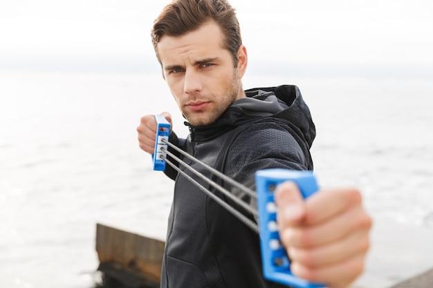 Przystojny, pewny siebie młody sportowiec na plaży, używając ekspandera do klatki piersiowej