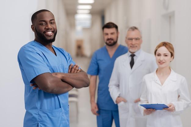Przystojny, pewny siebie pozytywny stażysta cieszący się procesem egzaminacyjnym w szpitalu i stojąc ze skrzyżowanymi rękami, podczas gdy inni koledzy stoją