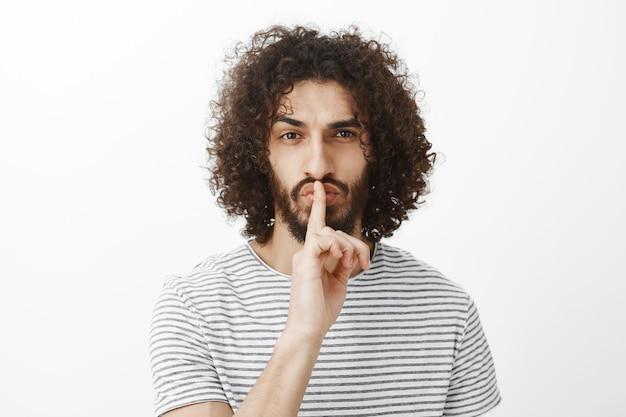Przystojny, pewny siebie współpracownik w stylowej koszulce w paski, wykonujący gest ciii, mówiący ucisz z palcem wskazującym na ustach, marszczący brwi, zabawny i skupiony