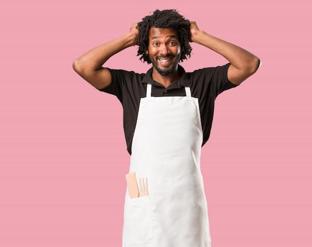 Przystojny piekarz african american szalony i zrozpaczony, krzyczy poza kontrolą