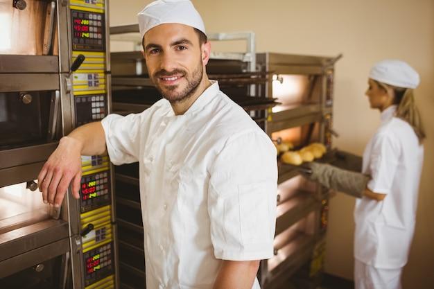 Przystojny piekarz uśmiecha się do kamery