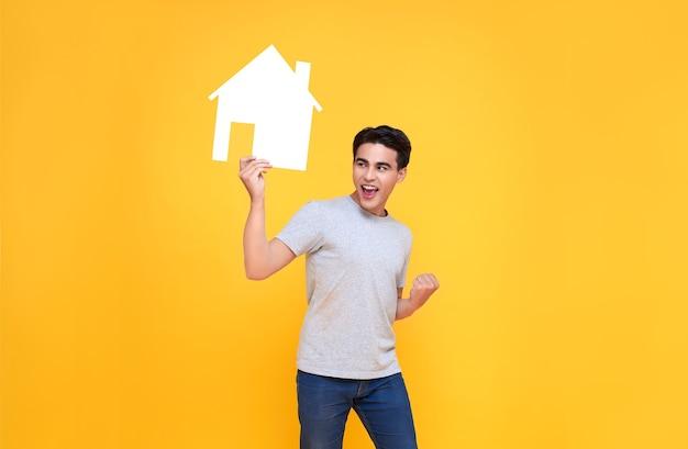 Przystojny podekscytowany azjatycki mężczyzna trzyma wyłącznik domu na białym tle na żółtym tle.