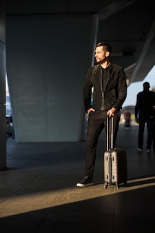 Przystojny podróżnik czekający na transport po przylocie
