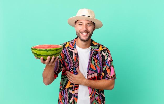 Przystojny podróżnik śmiejący się głośno z jakiegoś śmiesznego żartu i trzymający arbuza. koncepcja wakacje