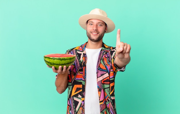 Przystojny podróżnik uśmiechający się dumnie i pewnie robiąc numer jeden i trzymając arbuza. koncepcja wakacje