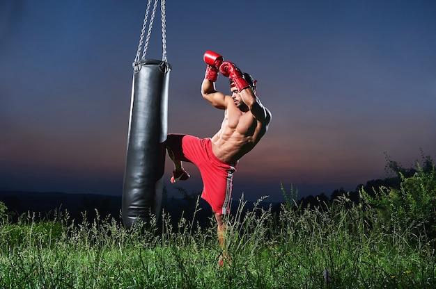Przystojny półnagi muskularny młody bokser ćwiczący z workiem treningowym na zewnątrz copyspace piękny zachód słońca na tle natura styl życia sport aktywny sportowiec atletyczny trening męskości.