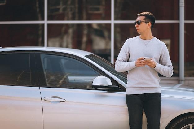 Przystojny pomyślny mężczyzna samochodem z telefonem komórkowym